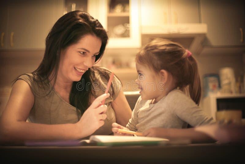 Madre que enseña a su niña a dibujar Cierre para arriba fotografía de archivo