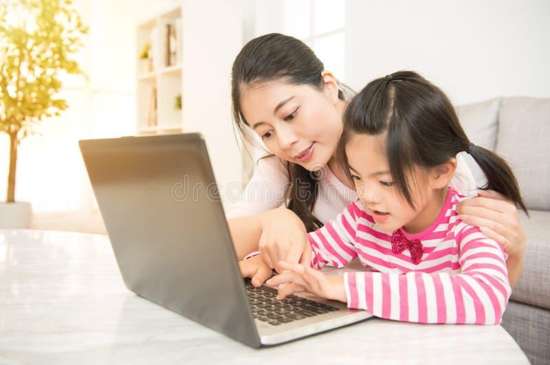 Madre que enseña a su ordenador de la hija fotografía de archivo libre de regalías