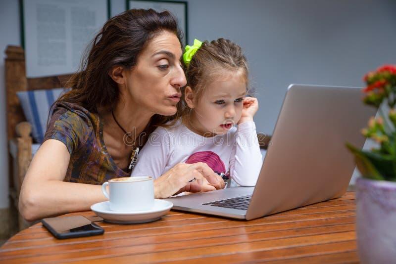Madre que enseña a su poca hija en el ordenador portátil fotografía de archivo
