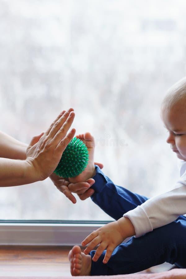 Madre que hace al hijo del masaje del pie foto de archivo