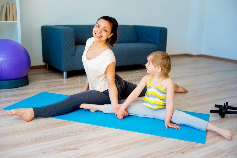 Madre que hace yoga con la hija imagen de archivo