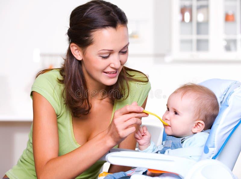 Madre que introduce al bebé hambriento foto de archivo libre de regalías