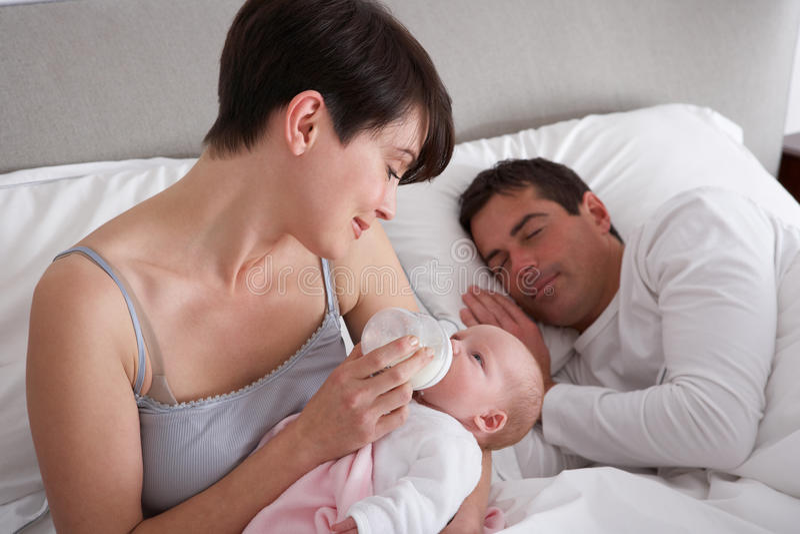 Madre que introduce al bebé recién nacido en cama en el país foto de archivo