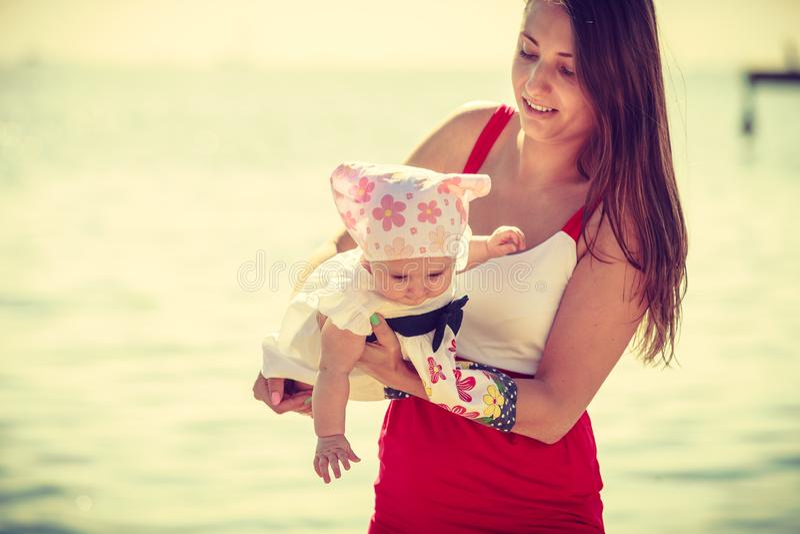Madre que juega con el bebé en la playa fotos de archivo