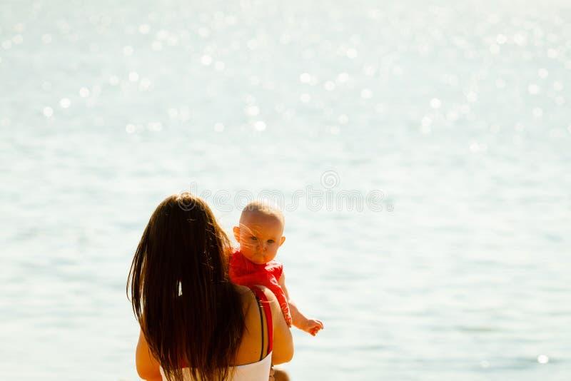 Madre que juega con el bebé en la playa imagenes de archivo