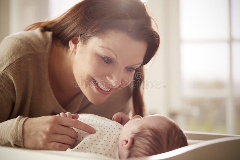 Madre que juega con el bebé recién nacido que miente en la tabla cambiante foto de archivo