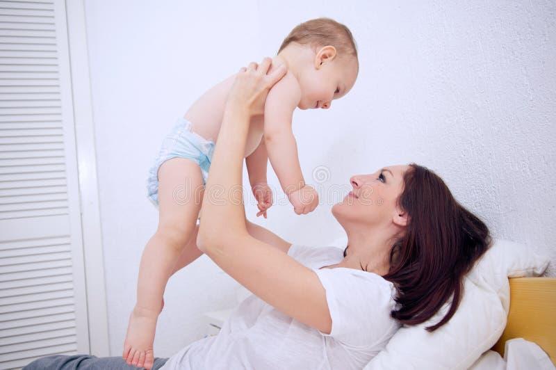 Madre que juega con su bebé fotos de archivo