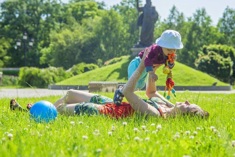 Madre que juega con su bebé en un gran día soleado en un prado con las porciones de hierba verde y de flores salvajes foto de archivo libre de regalías