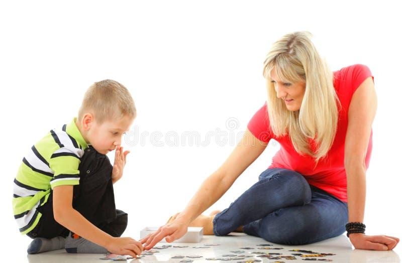 Madre que juega rompecabezas así como su hijo fotografía de archivo
