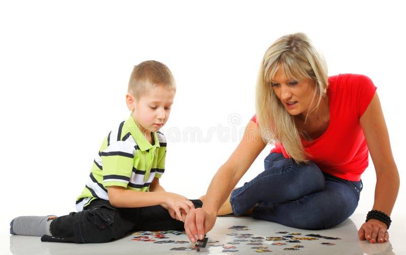 Madre que juega rompecabezas así como su hijo imagen de archivo libre de regalías