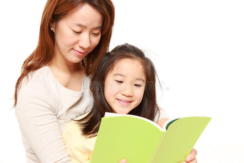 Madre que lee un libro a su hija fotografía de archivo libre de regalías