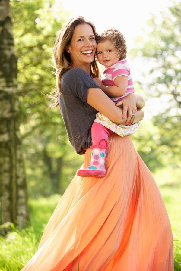 Madre que lleva a la hija joven imagen de archivo libre de regalías