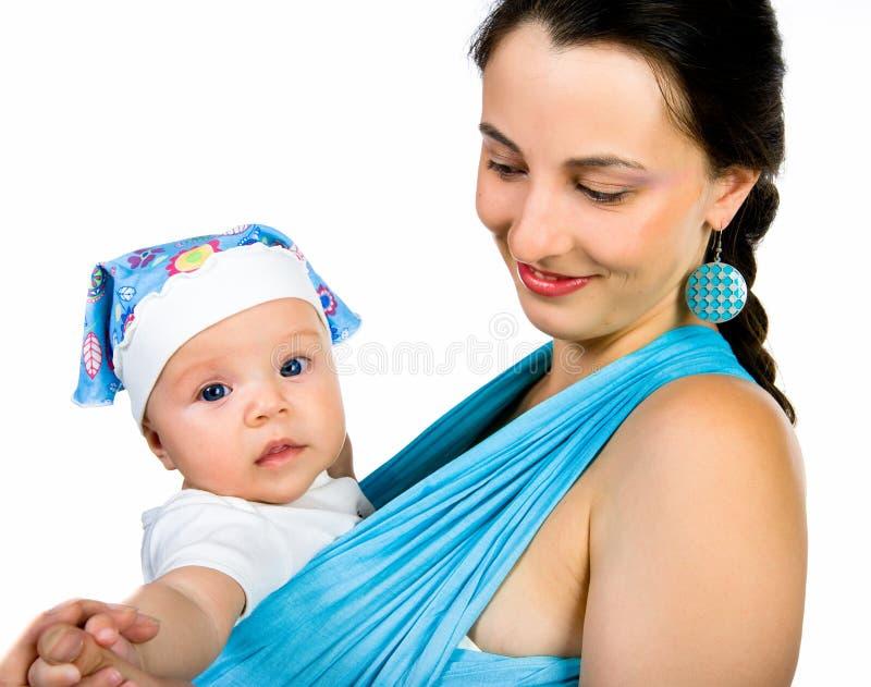 Madre que lleva a su bebé en una honda fotografía de archivo libre de regalías