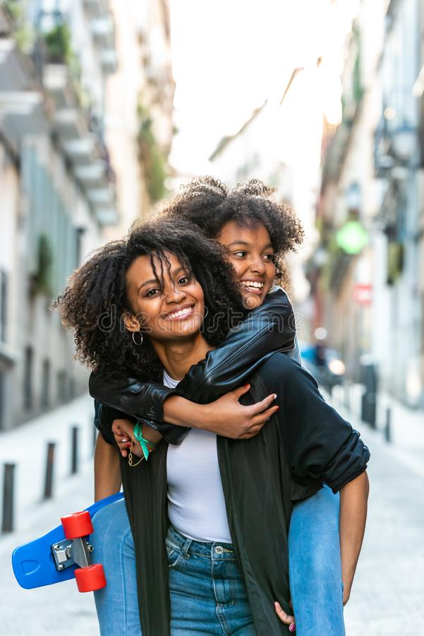 Madre que lleva a su hija en la parte posterior foto de archivo libre de regalías