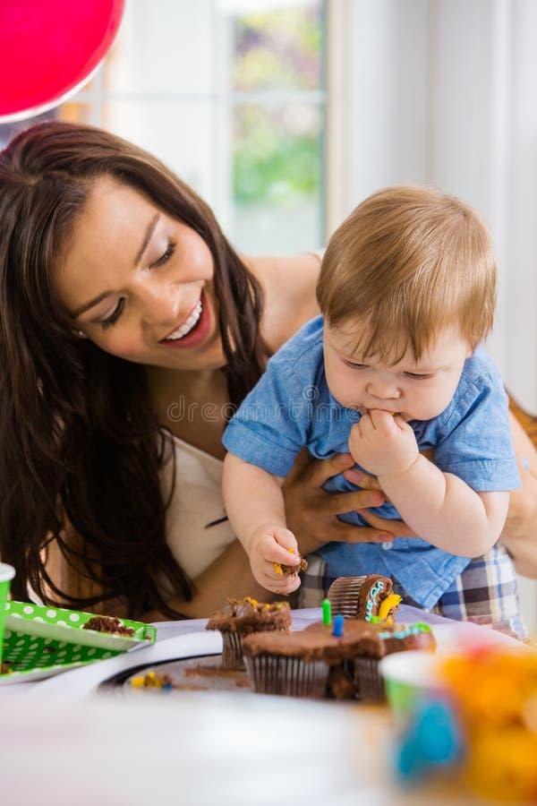 Madre que mira al bebé que come la magdalena fotos de archivo