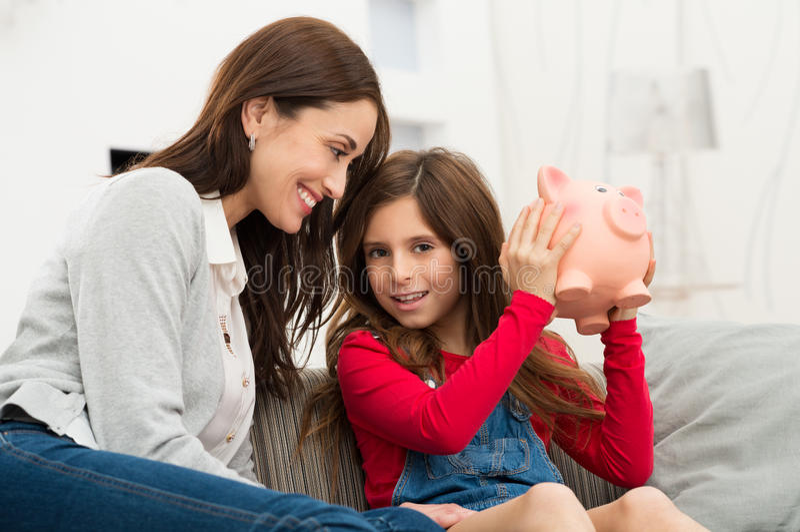 Madre que mira a la hija que sostiene Piggybank fotografía de archivo libre de regalías
