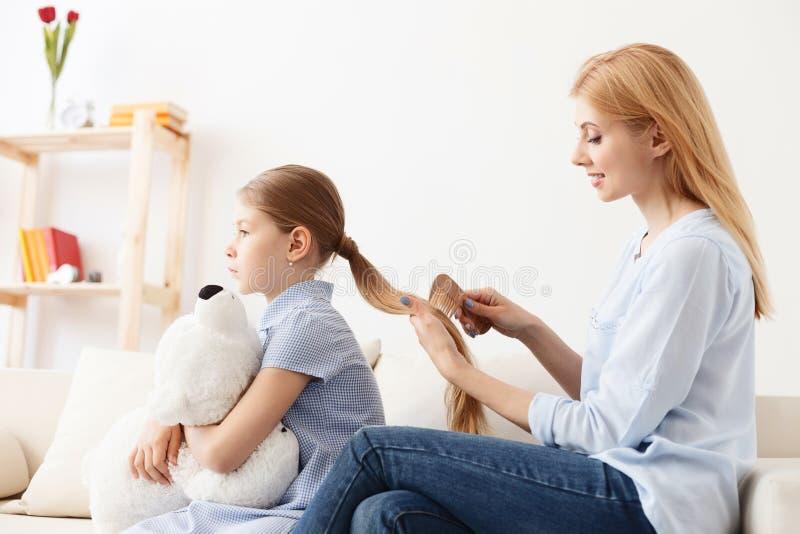 Madre que peina el pelo de la hija foto de archivo