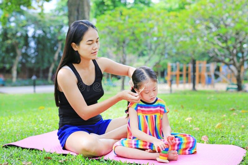 Madre que peina el pelo de la hija que miente en el jardín verde fotografía de archivo
