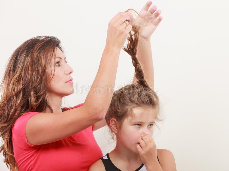 Madre que peina el pelo para la hija imagen de archivo libre de regalías