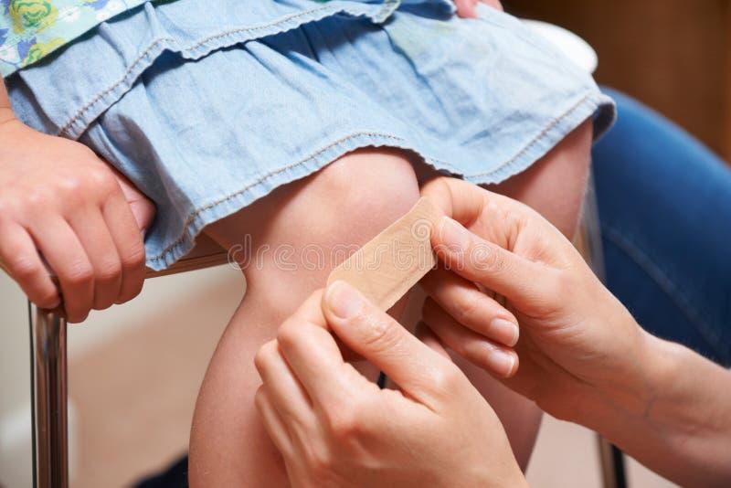 Madre que pone el vendaje adhesivo en la rodilla de la hija imagen de archivo libre de regalías
