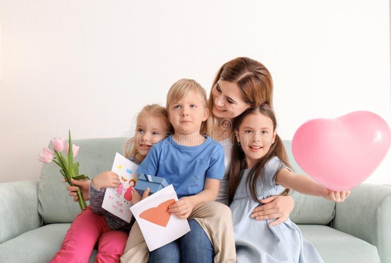 Madre que recibe los regalos de sus pequeños niños lindos en casa fotos de archivo libres de regalías