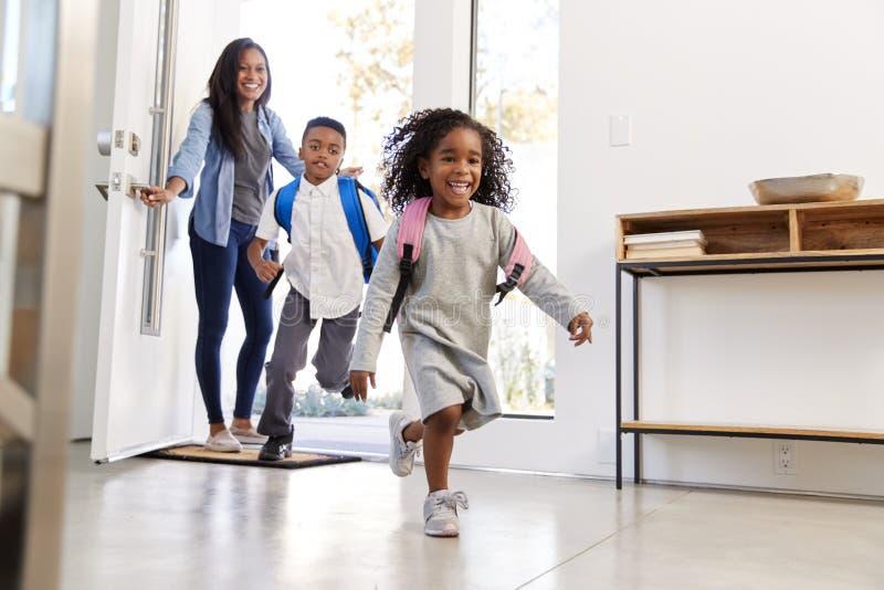 Madre que recoge y que trae el hogar del hijo y de la hija después de escuela fotografía de archivo libre de regalías