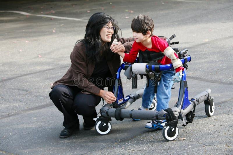 Madre que recorre con el hijo lisiado en caminante foto de archivo libre de regalías