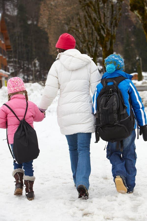 Madre que recorre dos niños a la escuela en nieve foto de archivo