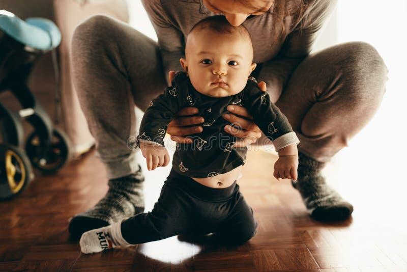 Madre que se pone en cuclillas en piso con su bebé imagen de archivo