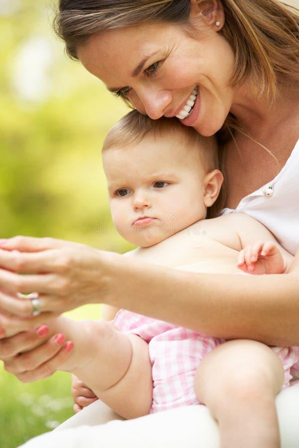 Madre que se sienta con el bebé en campo fotografía de archivo libre de regalías
