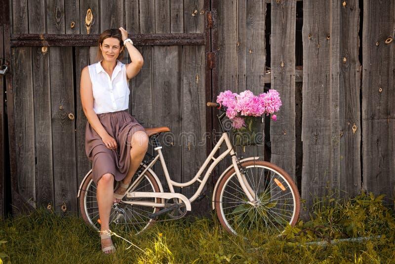 Madre que se sienta en la bicicleta retra beige imágenes de archivo libres de regalías