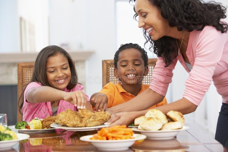 Madre que sirve una comida a sus niños imagenes de archivo
