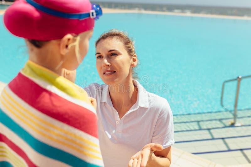 Madre que toma el cuidado de la muchacha después de nadar lecciones foto de archivo