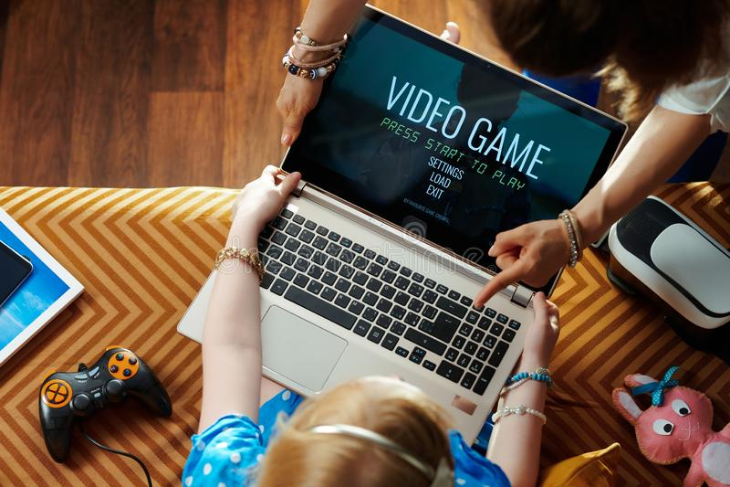 Madre que toma el ordenador portátil de enviciado a los videojuegos el niño imagen de archivo libre de regalías