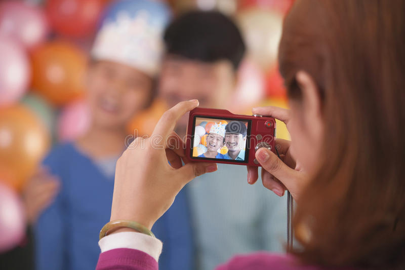 Madre que toma la foto del padre y del hijo en el cumpleaños del hijo imagen de archivo libre de regalías