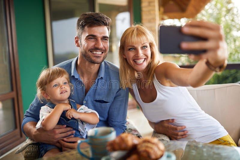 Madre que toma las fotos con la hija y el marido imagenes de archivo