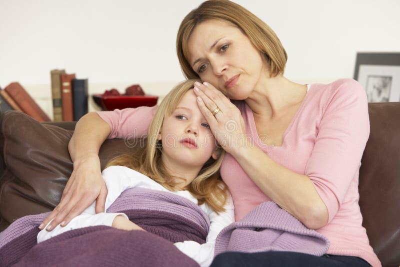 Madre que toma temperatura de la hija enferma imagenes de archivo