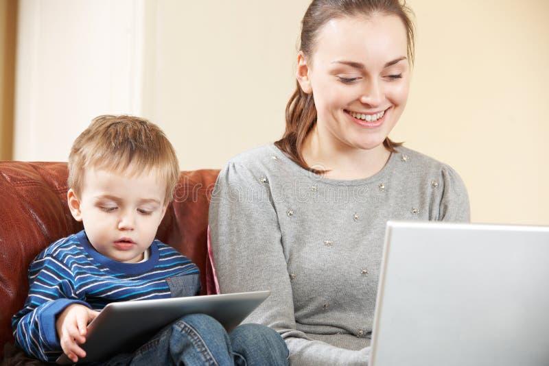 Madre que trabaja en el ordenador portátil mientras que el hijo utiliza la tableta de Digitaces fotografía de archivo libre de regalías