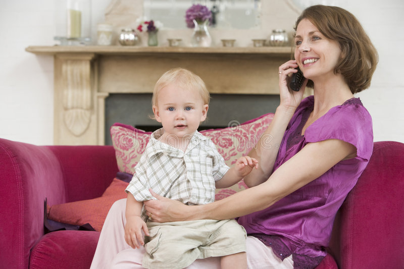 Madre que usa el teléfono en sala de estar con el bebé imágenes de archivo libres de regalías