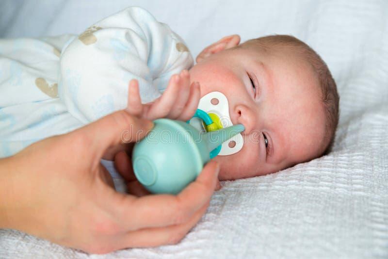 Madre que usa la jeringuilla del bulbo para limpiar la nariz del bebé foto de archivo libre de regalías