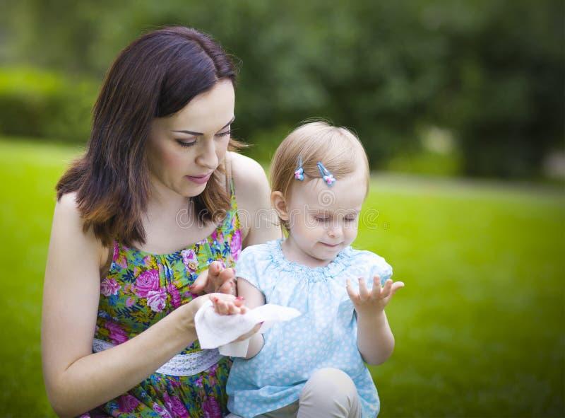 Madre que usa los trapos mojados para su hija imagen de archivo