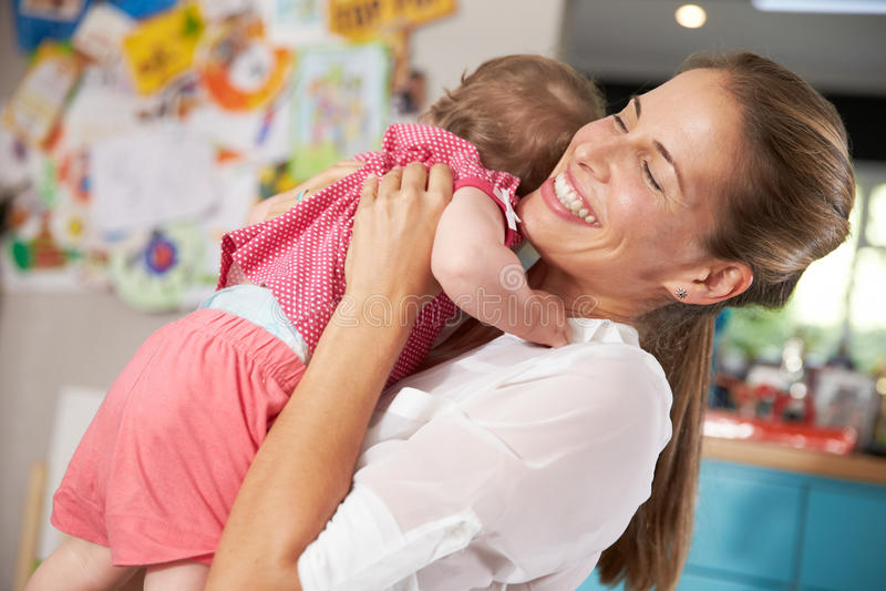 Madre que vuelve del trabajo que abraza a la hija joven fotografía de archivo