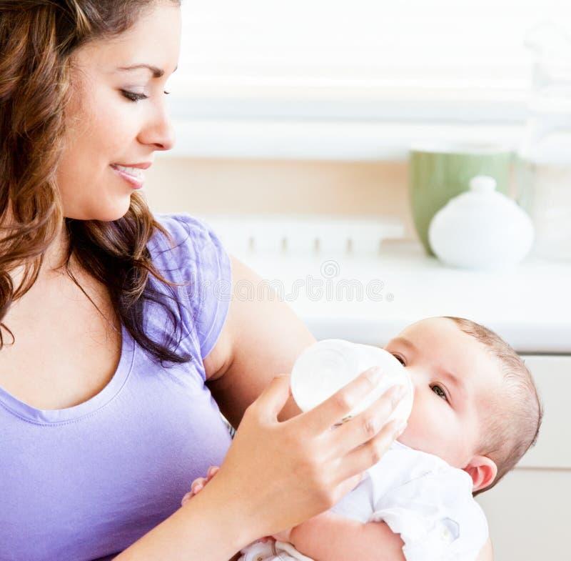 Madre radiante che alimenta il suo figlio adorabile nel paese fotografie stock libere da diritti