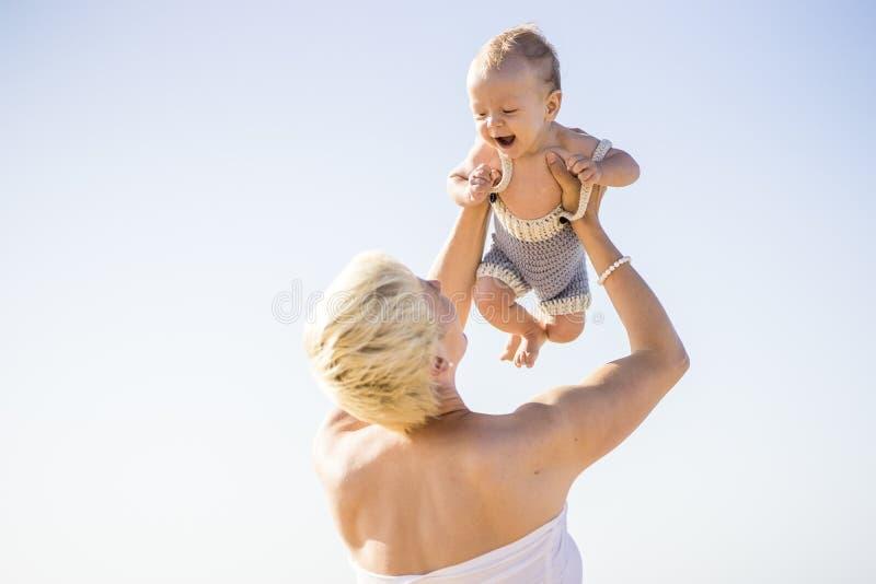 Madre rubia atractiva que soporta a su bebé lindo en el beac fotografía de archivo libre de regalías
