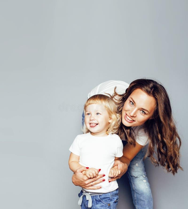 Madre rubia sonriente moderna joven con la pequeña hija linda en w imagen de archivo libre de regalías