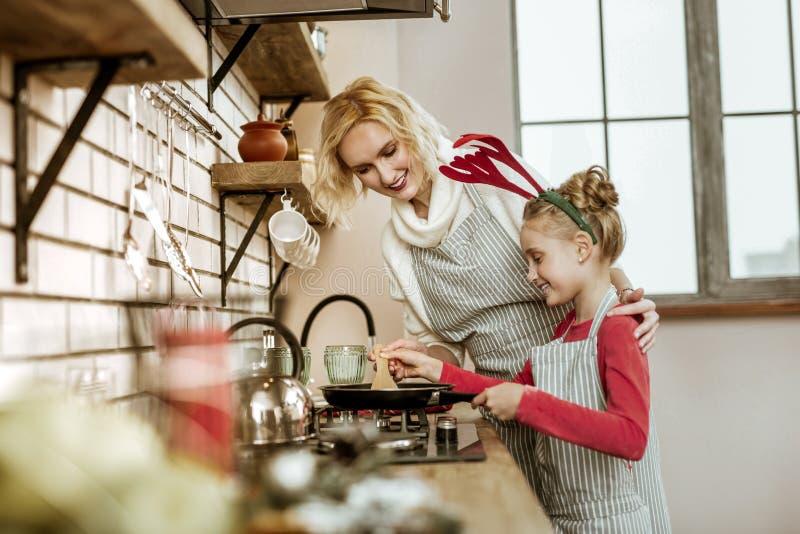 Madre rubia sonriente y su hija de emisión que se colocan cerca foto de archivo