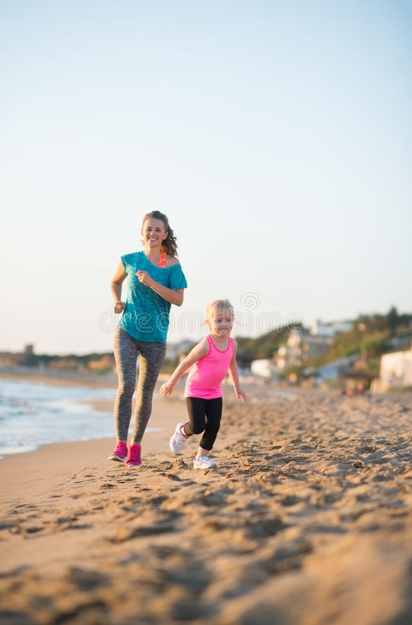 Madre sana y bebé que corren en la playa fotografía de archivo