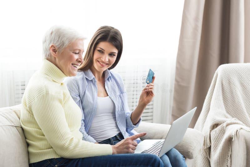 Madre senior che compera online con sua figlia immagine stock libera da diritti