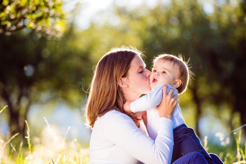 Madre, sentándose en la hierba, besando a su pequeño hijo foto de archivo libre de regalías