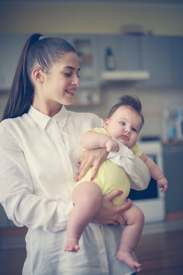 Madre single che sta nella cucina e che tiene la sua piccola b fotografia stock libera da diritti